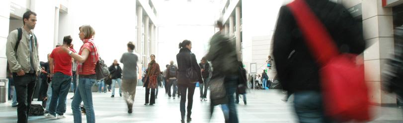 Une étudiante au sac rouge marche dans le hall d'Uni-Mail.
